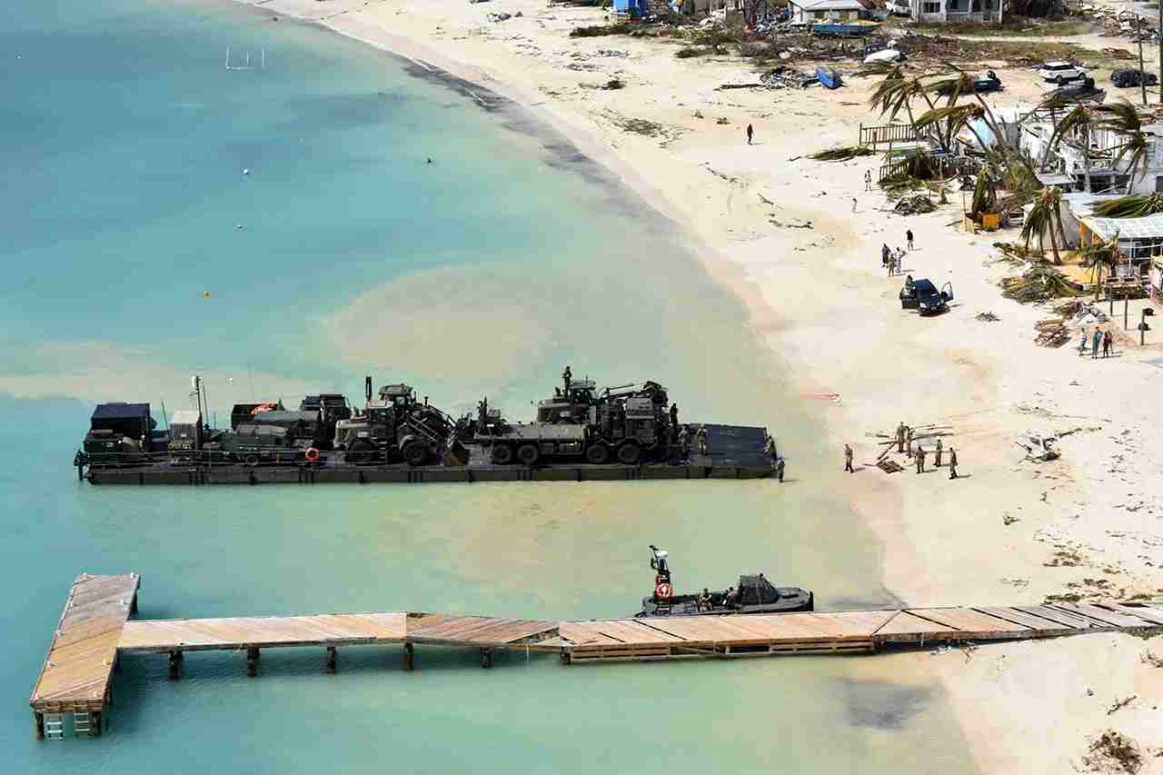 A RLC Mexeflote approaches Sandy Bay Village beach, in Anguilla loaded with the 2 JCBs, 1 flatbed lorry, fork lift truck, BV 206 multi terrain vehicle, a Land Rover and a mobile generator in early September 2017. (Royal Navy/Ministry of Defence via AP)