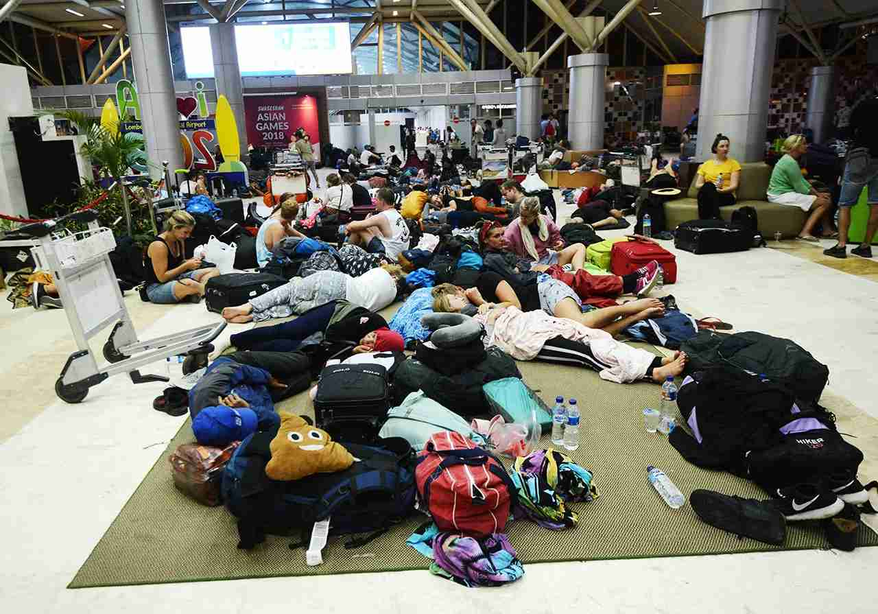 Foreign tourists sleep on the floor as they wait to depart from the Praya Lombok International Airport on the West Nusa Tenggara province on August 6, 2018. - Indonesia sent rescuers fanning out across the holiday island of Lombok and evacuated more than 2,000 tourists after a powerful earthquake killed at least 98 people and damaged thousands of buildings. (Photo by SONNY TUMBELAKA / AFP) (Photo credit should read SONNY TUMBELAKA/AFP/Getty Images)