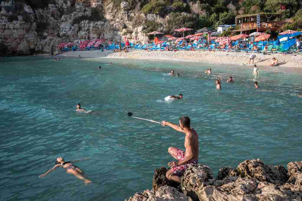 On 24 August 2018, a man with a selfie stick takes photos of a woman floating in the water at Buyukcakil beach a natural cove along the Mediterranean coast near the village of Kas in Antalya, Turkey, also known as the Turkish Riviera, which has an economy heavily dependent on the tourism industry, foreign visitors. (Photo by Diego Cupolo/NurPhoto via Getty Images)