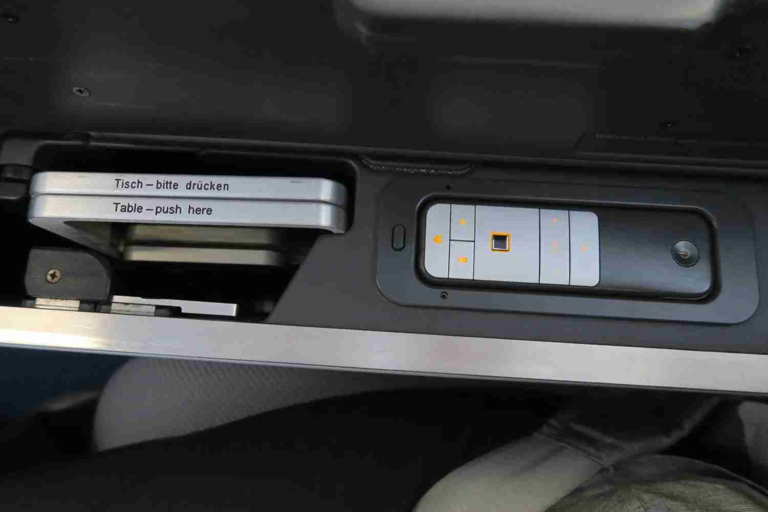 The tray table and IFE remote are stored in the center console.