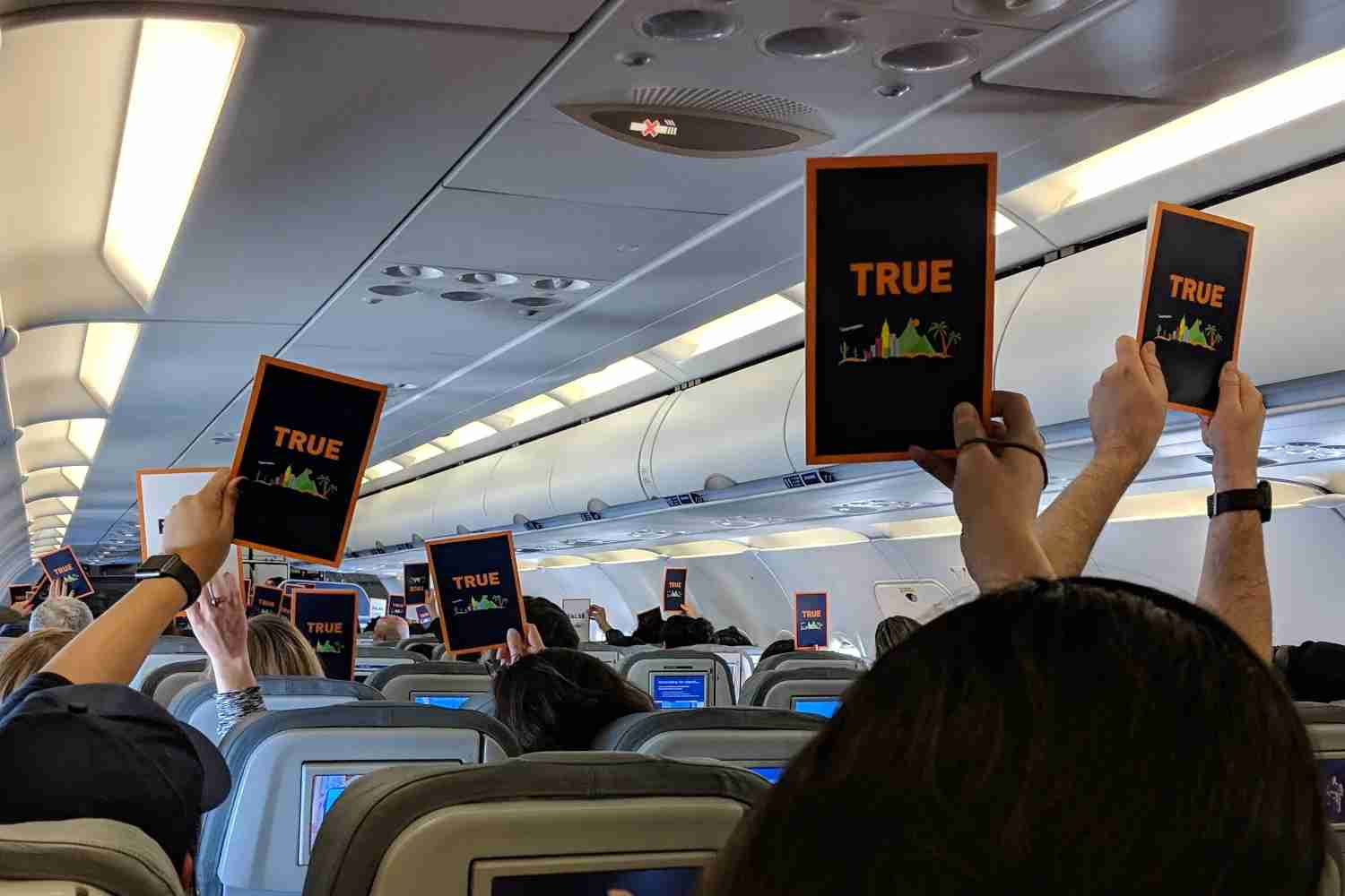 Holding up True / False cards in the onboard trivia game.