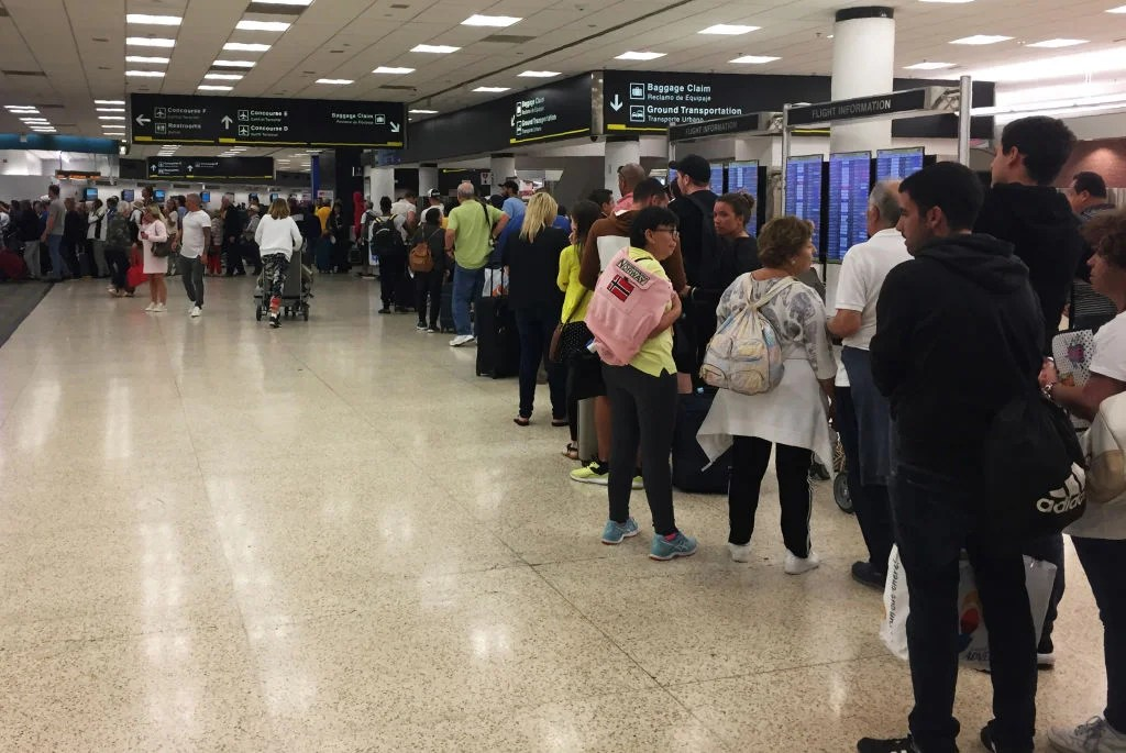 Passengers flying from Miami International Airport wait in line to enter the checkpoint at Concourse F, where some of the flights of a closed terminal were diverted, in Miami, Florida, on January 13, 2019. - Operations at Concourse G were shut down during the weekend due to a shortage of security agents sparked by the partial US government shutdown. (Photo by Leila MACOR / AFP) (Photo credit should read LEILA MACOR/AFP/Getty Images)