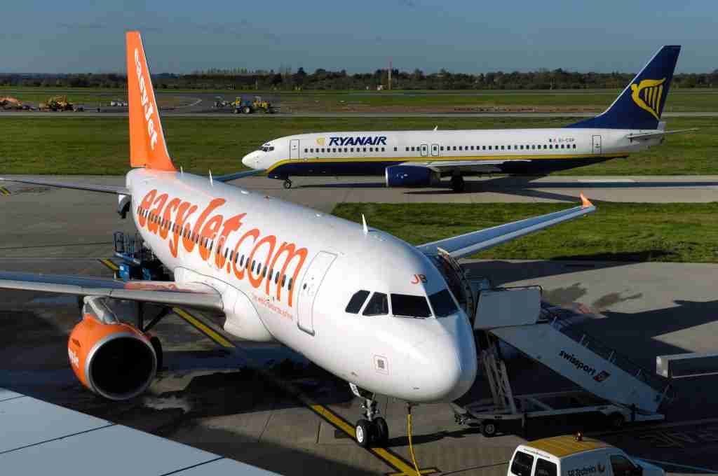 an easyJet Airbus A319-100 with Ryanair Boeing 737-800 taxiing and diggers and construction vehicles behind. (Photo by: aviation-images.com/UIG via Getty Images)