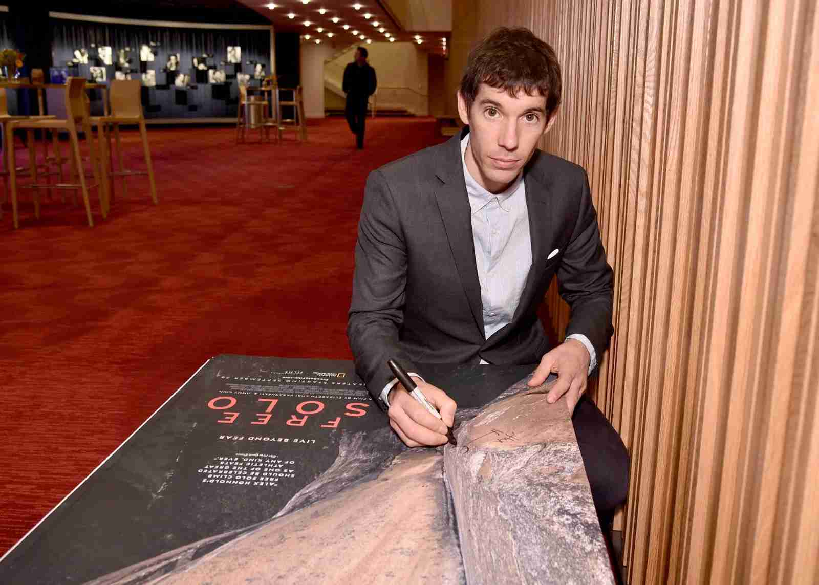 Featured Free Soloist Alex Honnold signs posters during the New York City premiere of National Geographic Documentary Films