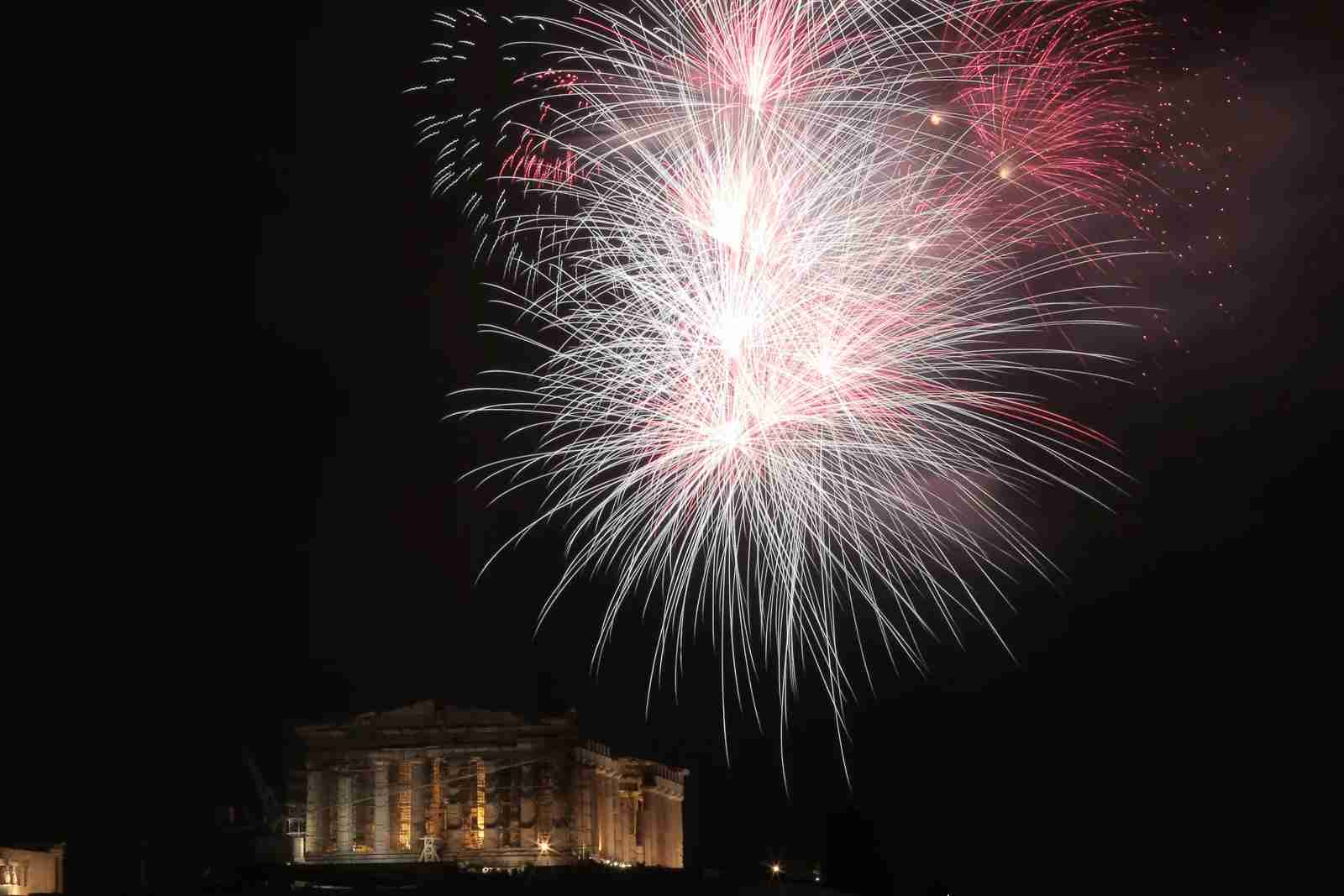 Fireworks explode over the Parthenon temple atop the Athens Acropolis hill during New Year
