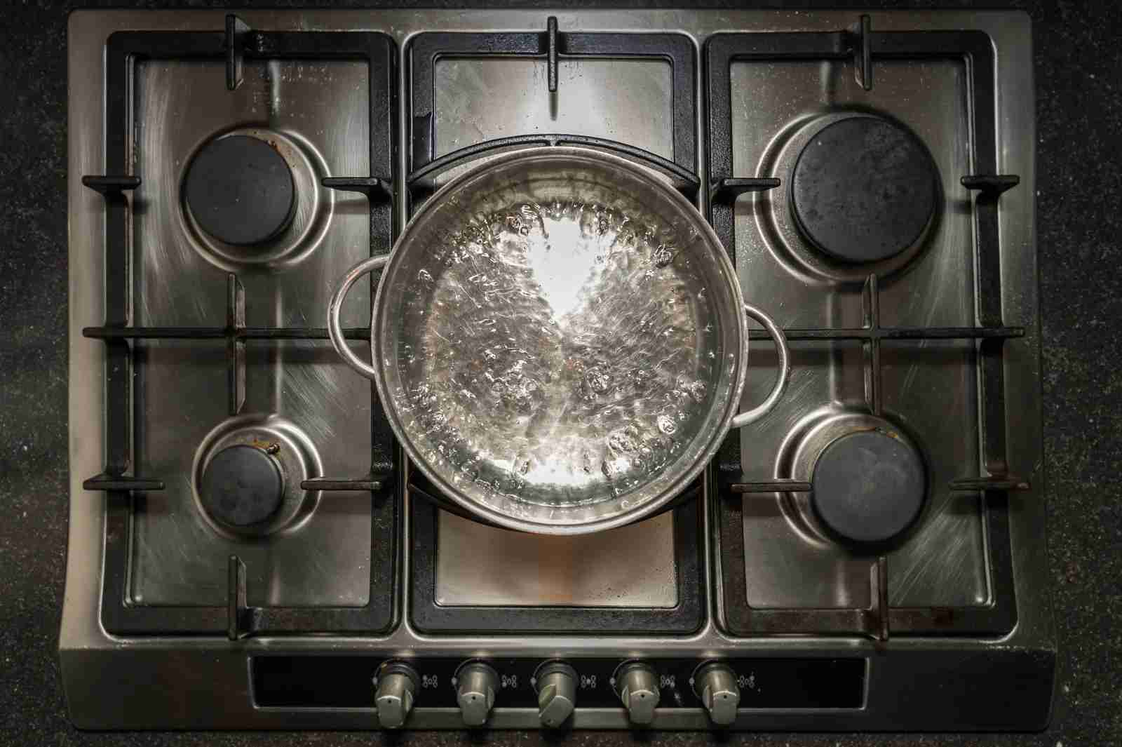 Metal cooking pan with boiling water and on a cooker, stove