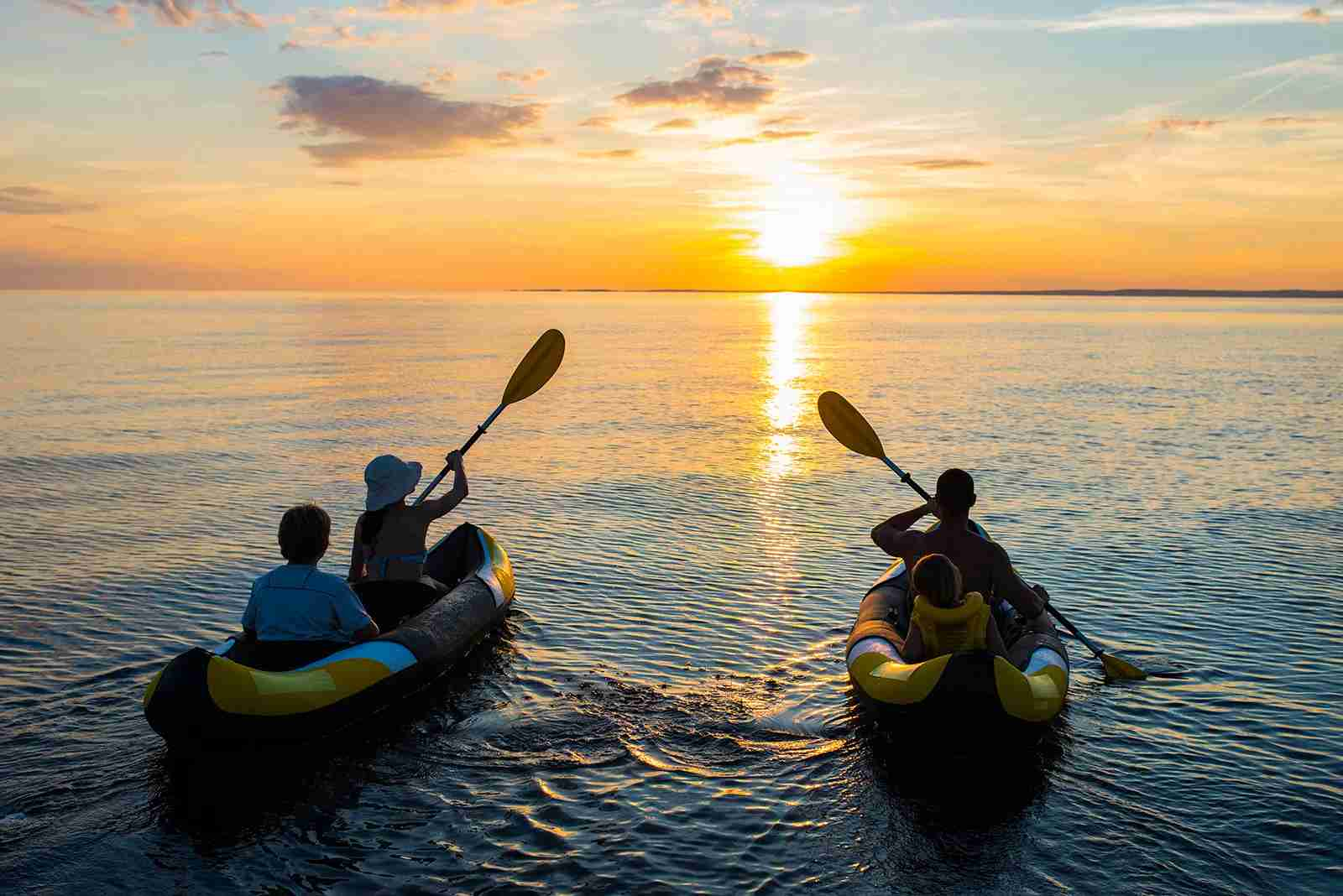 Family enjoying the sunset kayak tour. (Photo by simonkr/ Getty Images)