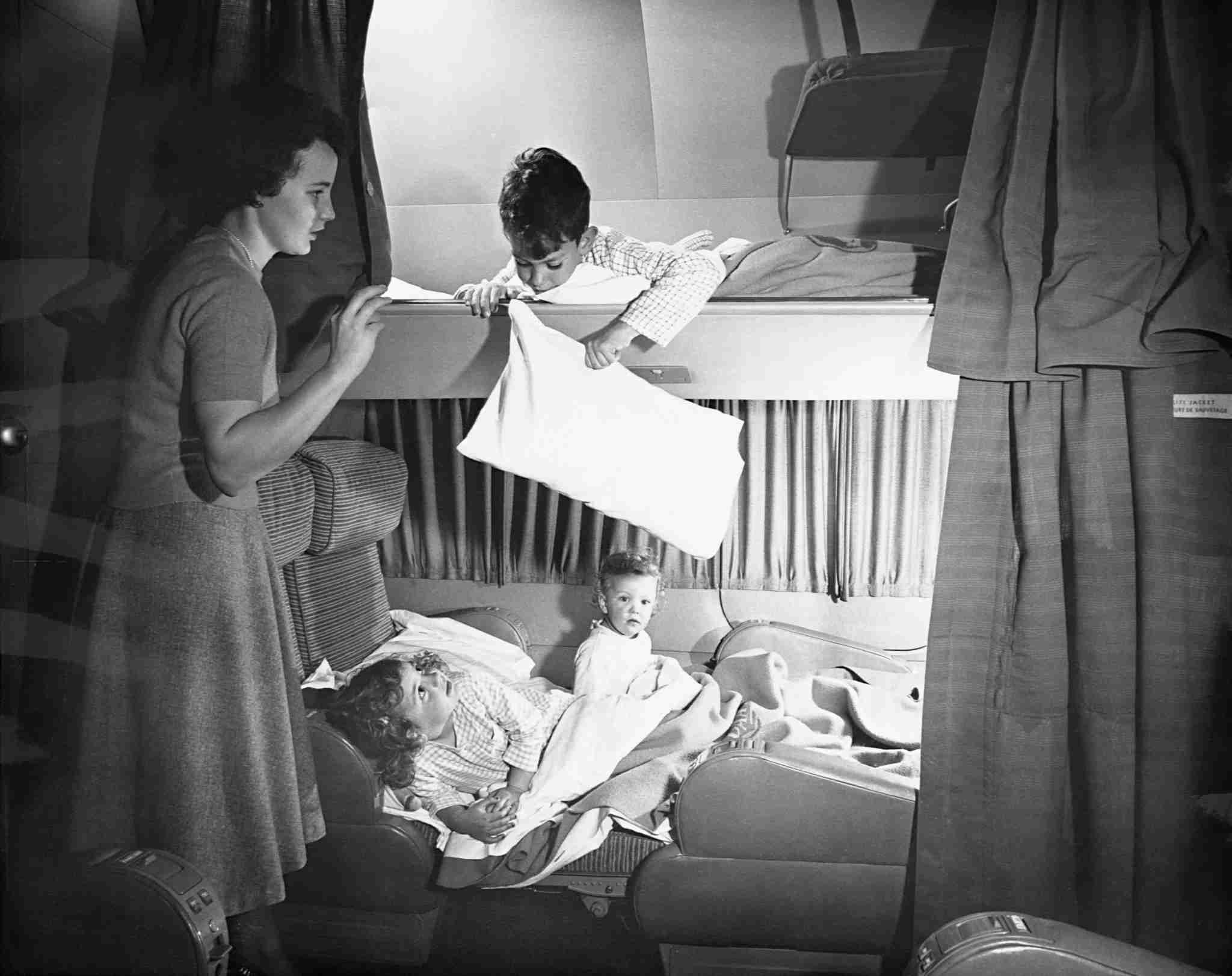 A mother tucks in her children in bunks aboard a Pan American Airways