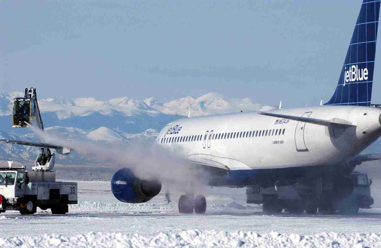 DENVER - DECEMBER 22:  De-Icing crews remove snow and ice from a plane that has been grounded due to a recent blizzard at Denver International Airport December 22, 2006 in Denver, Colorado. On Friday the clean-up began after the storm left thousands of travelers stranded and also caused a shut down of the city and highways exiting Denver.. (Photo by Thomas Cooper/Getty Images)