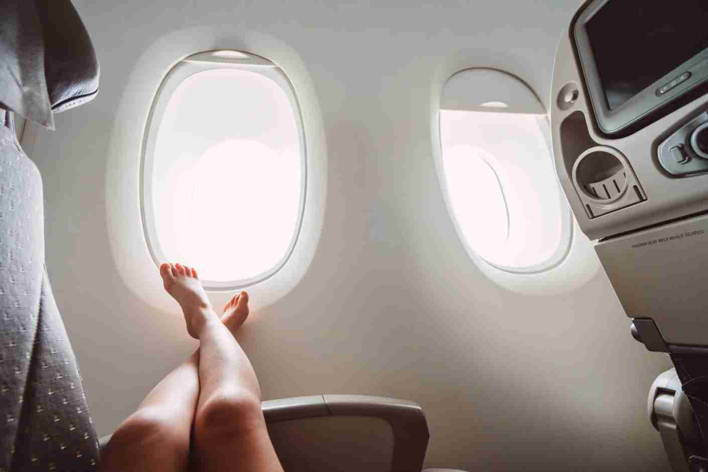 Sitting in the same position for a long period of time, like on an airplane, can be detrimental to your health. (Photo by Tang Ming Tung / Getty Images)
