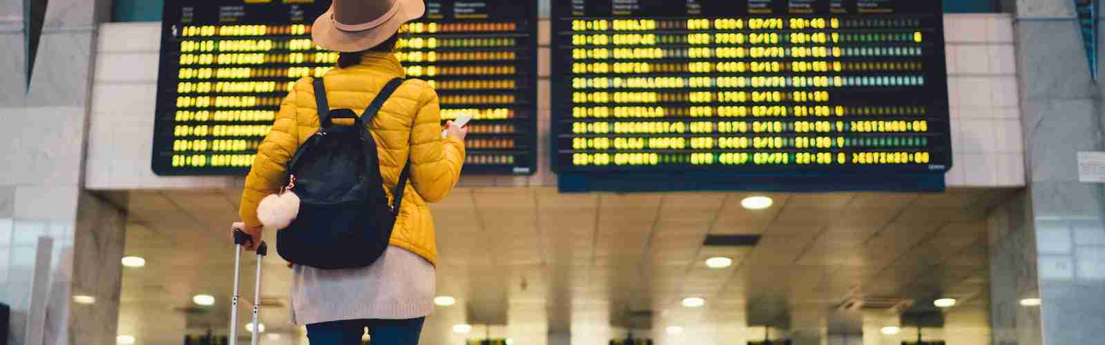 Female tourist with bag waiting airport flight stats