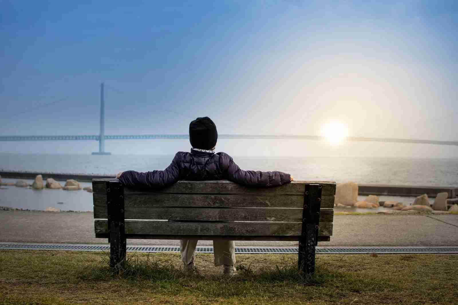 Sitting on park bench overlooking bridge over water