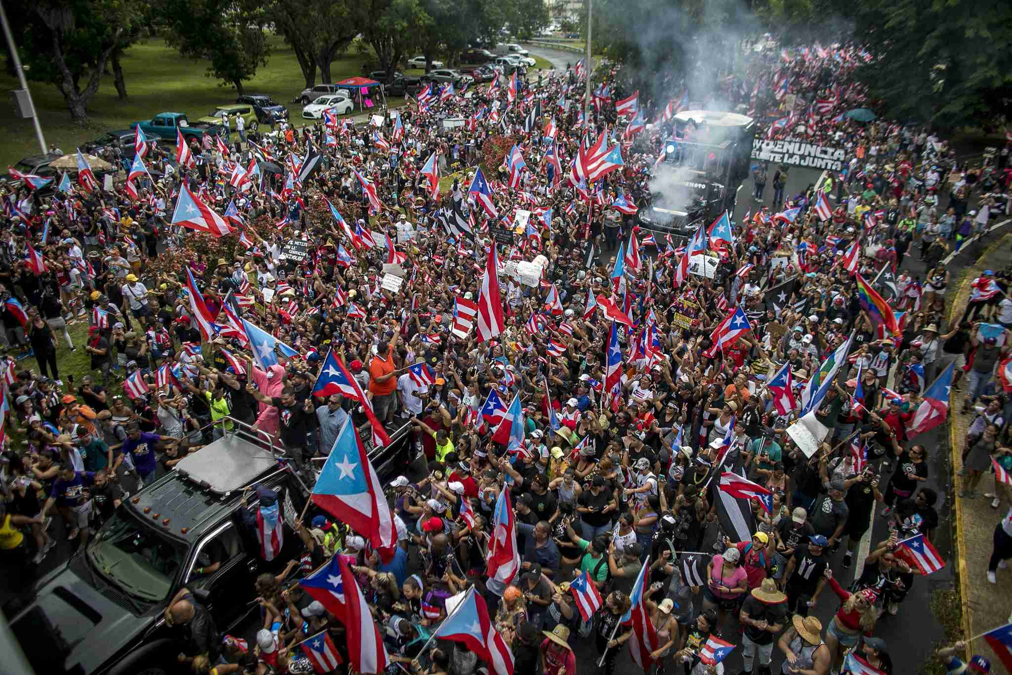 Attendees wave Puerto Rican flags during a celebration following Governor Ricardo Rossello