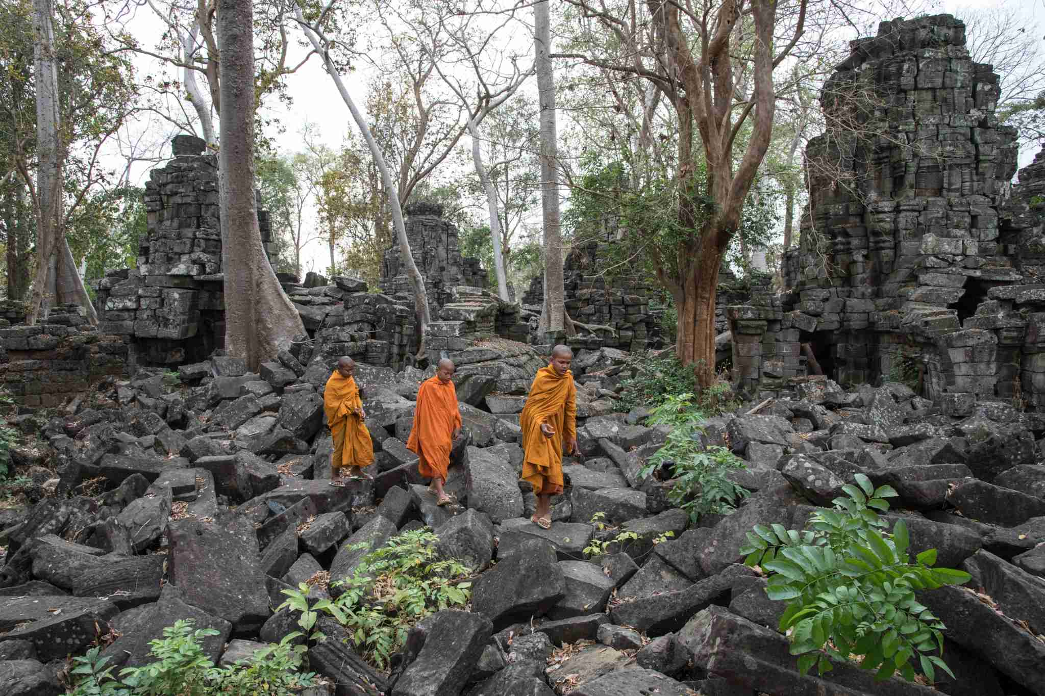 BANTEAY CHHMAR, BANTEAY MEANCHEY, CAMBODIA - 2015/02/18: Young Buddhist monks walk in the central sanctuary of Banteay Chhmar temple. The temple, built in the 12th century by king Jayavarman VII and located 150 kilometers north west of Angkor, is one of the largest of the Khmer empire. It is considered as a prototype for the famous Angkor Thom