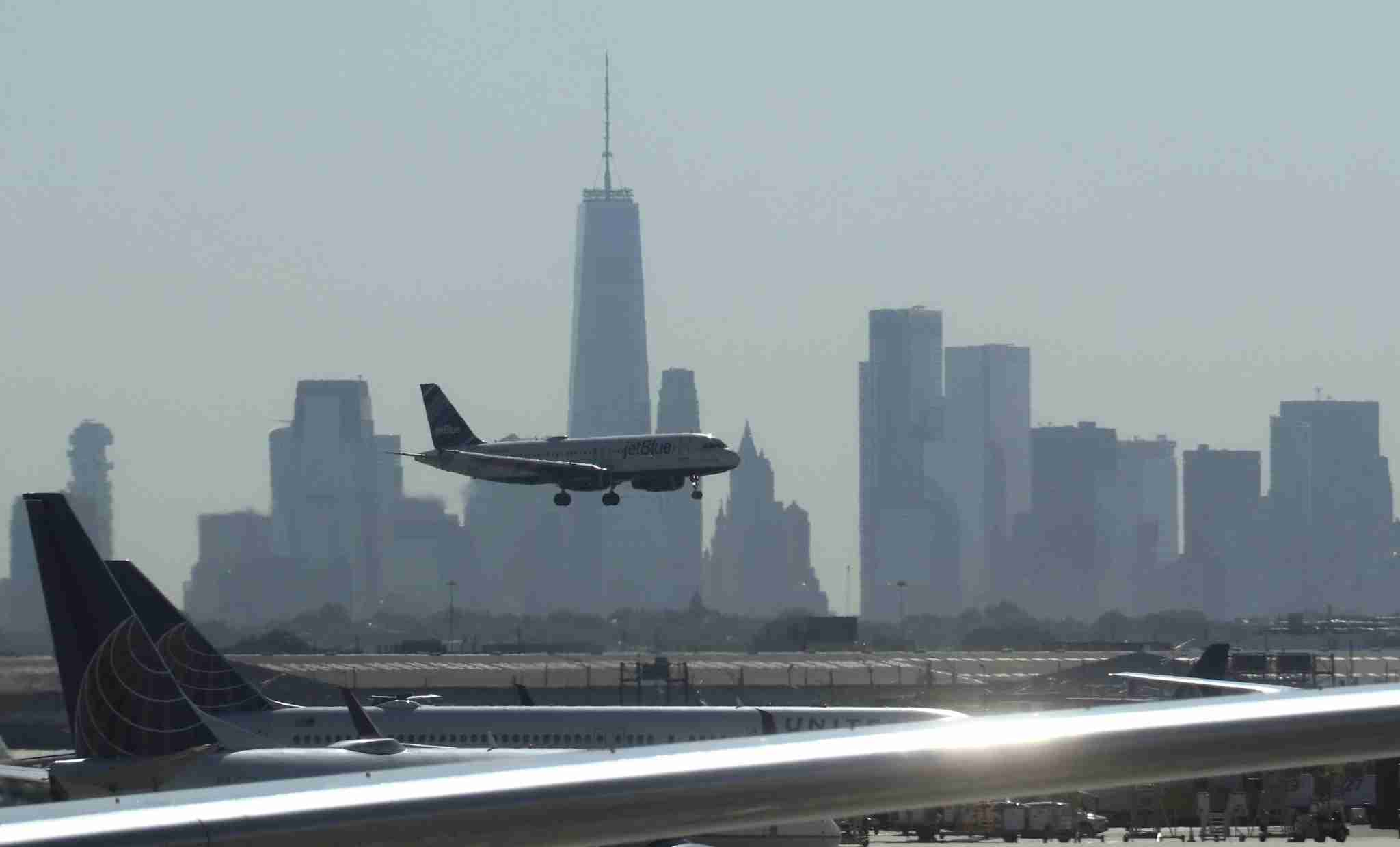 NEWARK, NJ - JUNE 14: A JetBlue airplane lands at Newark Liberty International Airport in front of lower Manhattan and One World Trade Center on June 14, 2018 in Newark, New Jersey. (Photo by Gary Hershorn/Getty Images)