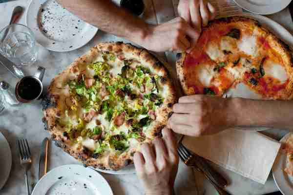 Hands dig in to two pizzas (1 margherita, 1 with brussels sprouts and pancetta) on a marble table. Photo by Michael Berman)