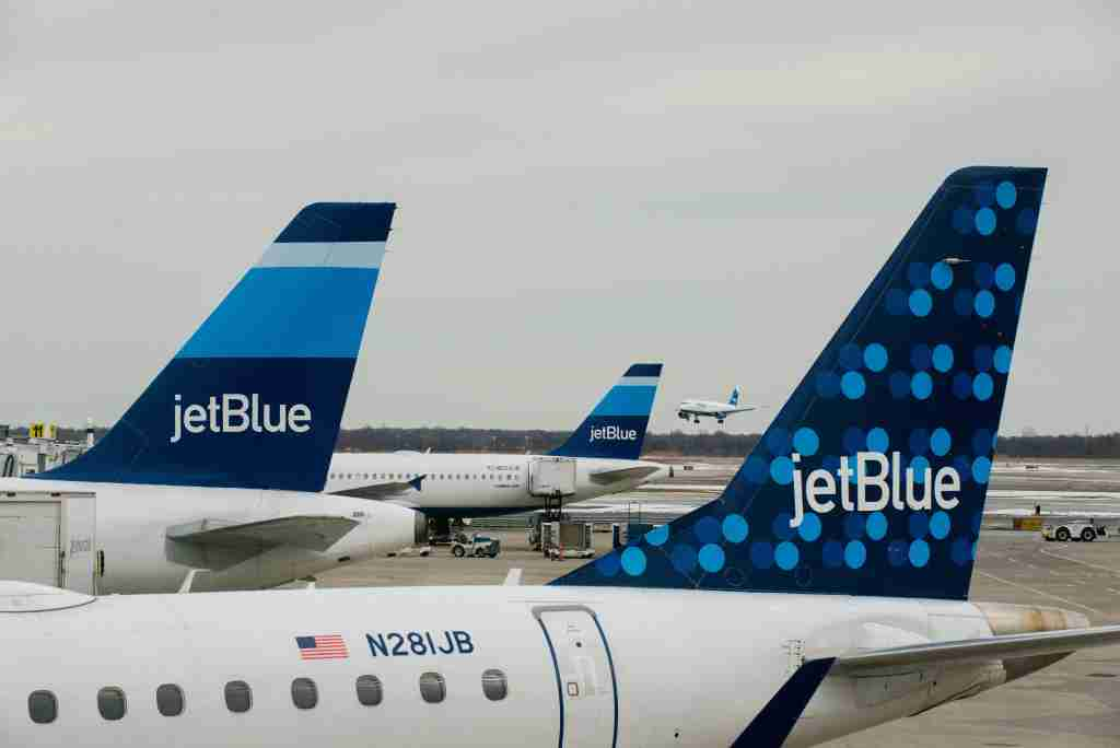 JetBlue Airways Corp. planes sit docked at the gates of Terminal 5 as another of the company