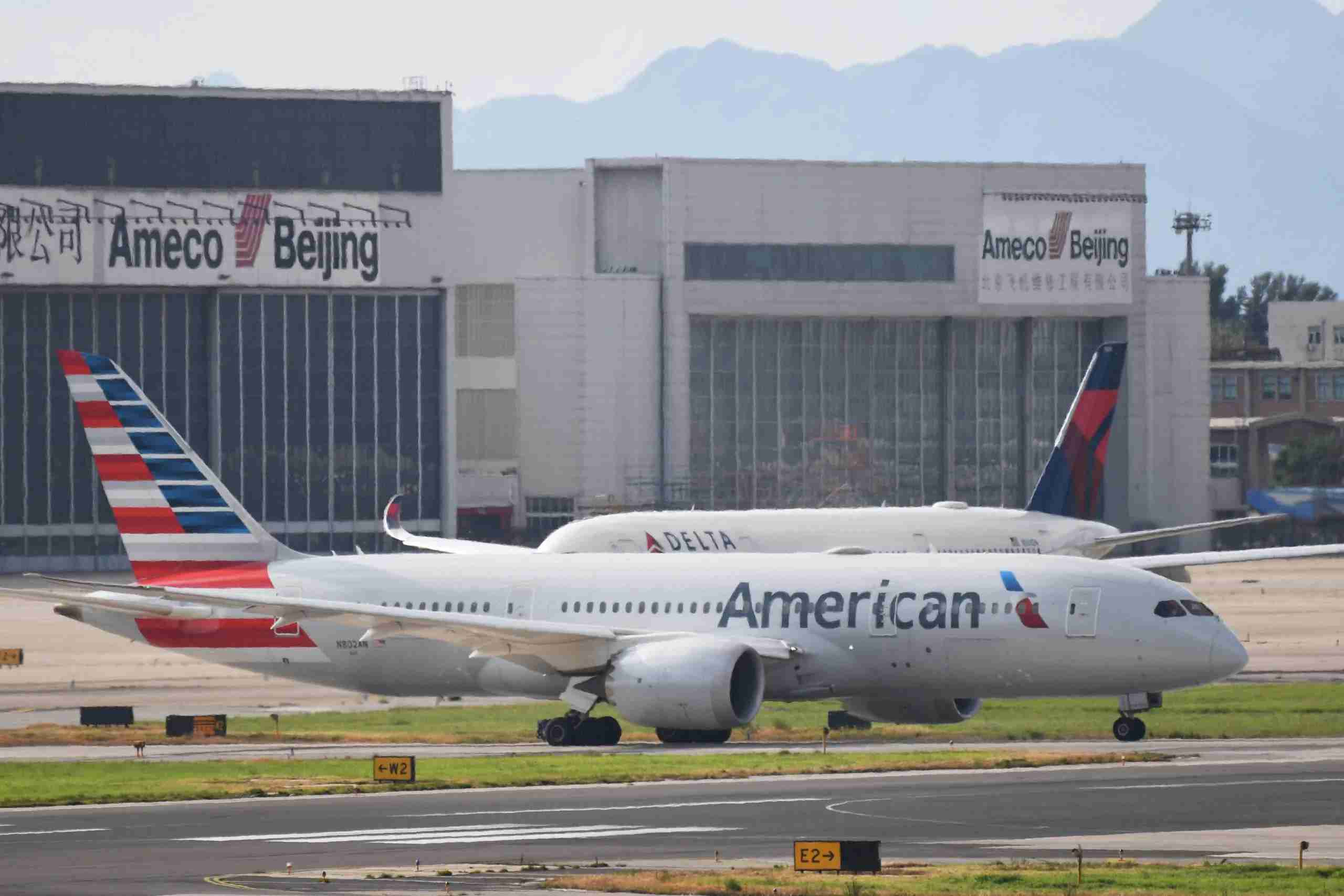 """An American Airlines Boeing 787 (front) and Delta Airlines Airbus A350 aircraft (background, obscured) wait to take off at Beijing airport on July 25, 2018. - Beijing hailed """"positive steps"""" as major US airlines and Hong Kong"""