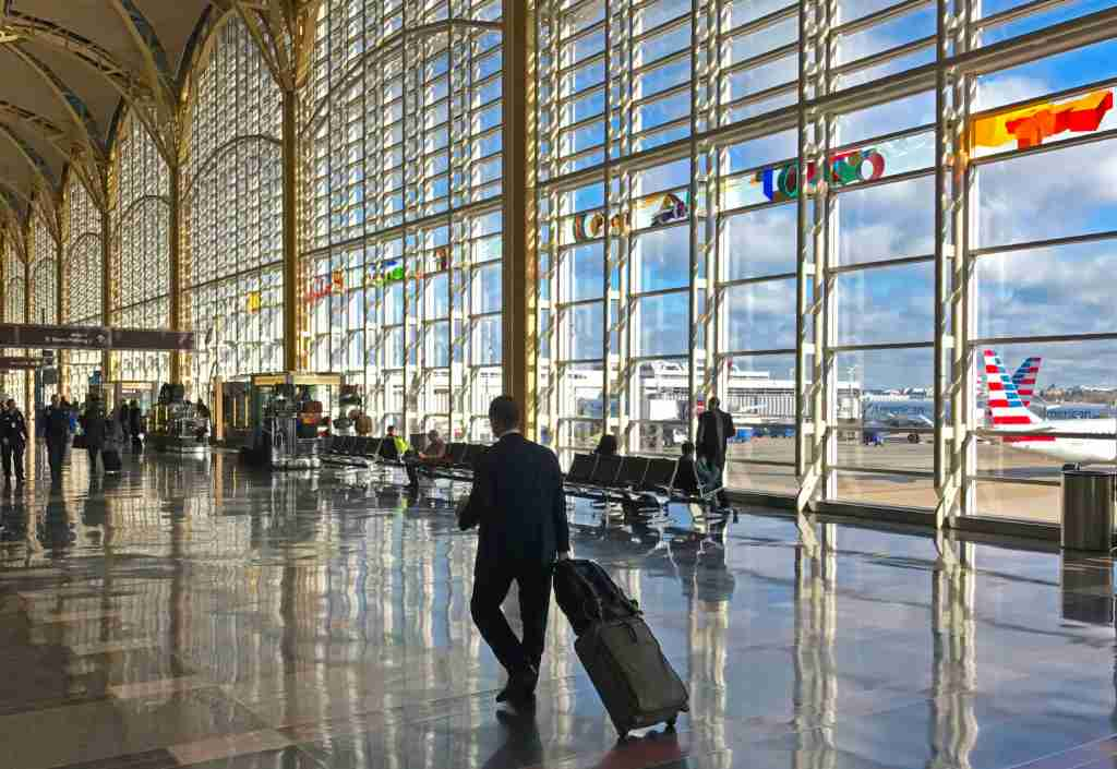 A traveler walks through the main hall at Ronald Reagan Washington National Airport in Arlington County, Virginia, 3 miles (5 km) south of Washington, DC 24, 2017. / AFP PHOTO / Daniel SLIM (Photo credit should read DANIEL SLIM/AFP via Getty Images)