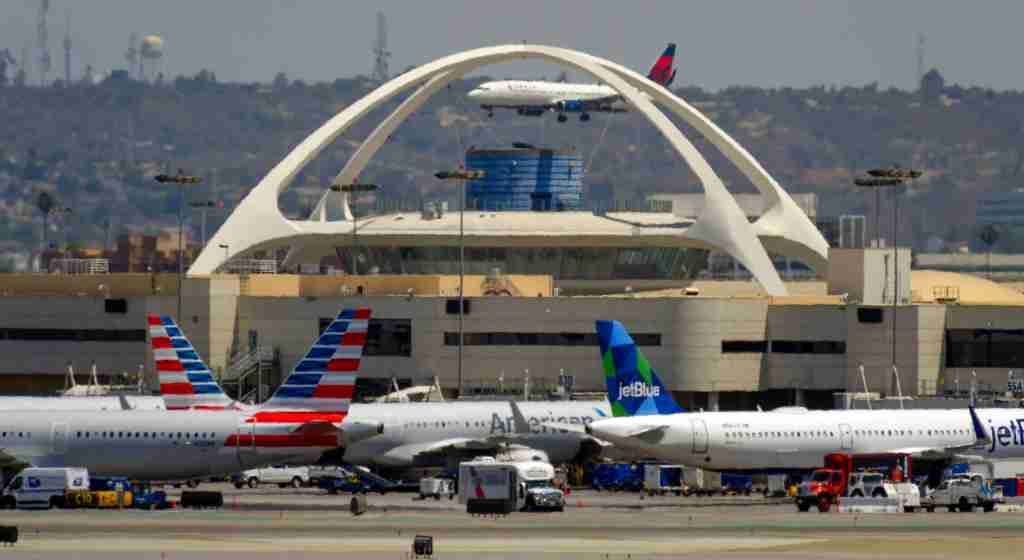 LOS ANGELES, CA - AUGUST 03: A planes sit at their gates, a Delta airline lands behind the theme building at LAX in Los Angeles on Thursday, August 3, 2017. The EPA says aircrafts account for a tenth of the nation
