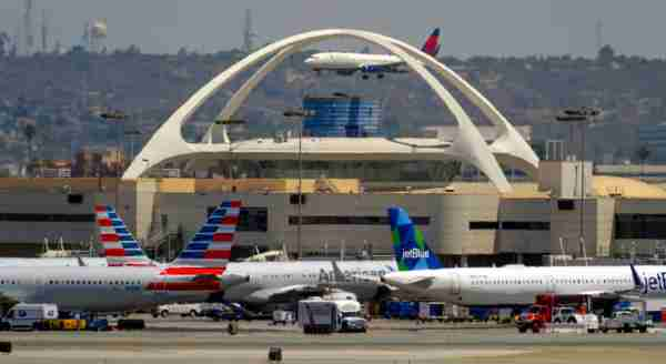 LOS ANGELES, CA - AUGUST 03: A planes sit at their gates, a Delta airline lands behind the theme building at LAX in Los Angeles on Thursday, August 3, 2017. The EPA says aircrafts account for a tenth of the nation's transportation related greenhouse gasses. And there's an international effort afoot to cut down pollution created in the air. (Photo by Scott Varley/Digital First Media/Torrance Daily Breeze via Getty Images)