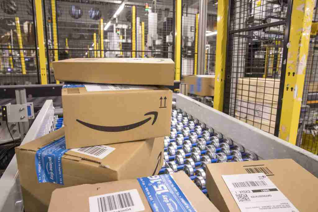 Packed boxes pass along a conveyor belt at the Amazon.com Inc. fulfilment centre in Tilbury, U.K. on Friday, July 12, 2019. By offering 12 extra hours of deals during this year