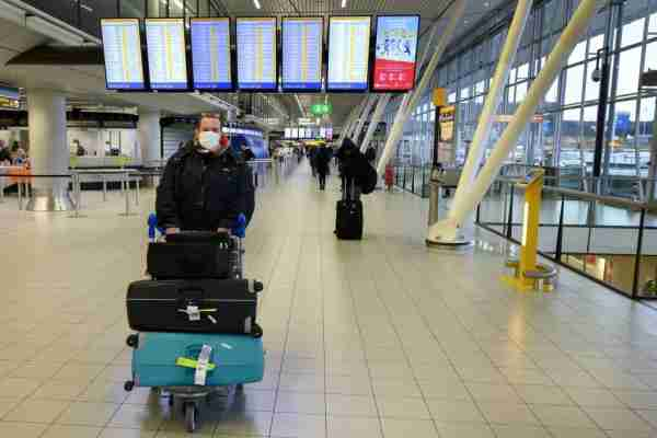 A traveler wearing a protective face masks pushes his luggage on a cart in Amsterdam Schiphol airport on February 2, 2020. - A number of airlines, including Netherlands