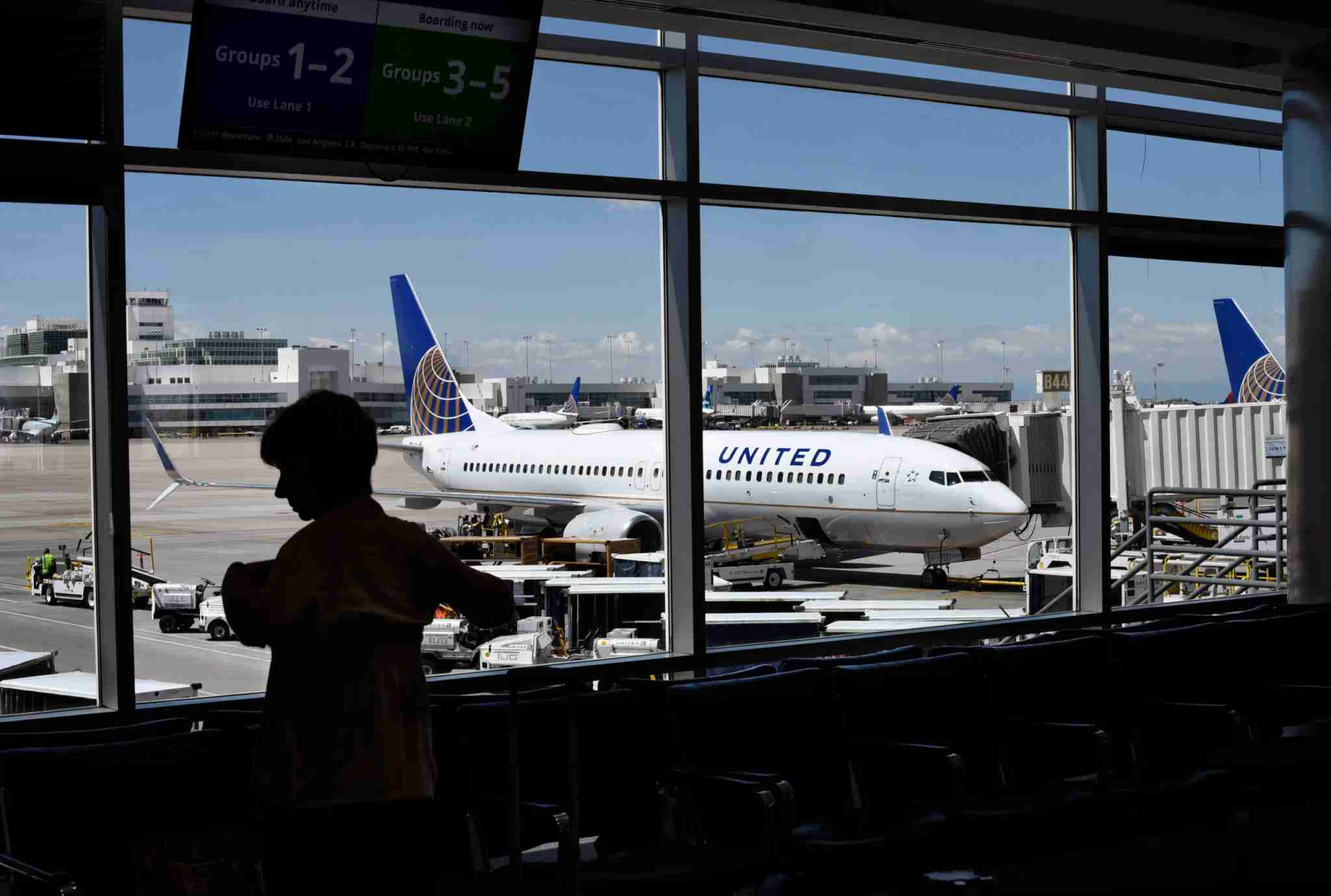 DENVER, COLORADO - JUNE 12, 2019: A passenger waiting for her flight to board stands in the airport terminal as a United Airlines plane is loaded at a gate at Denver International Airport in Denver, Colorado. (Photo by Robert Alexander/Getty Images)