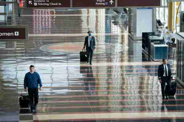 ARLINGTON, VA - MAY 05: A pilot wears a face covering as he walks through a mostly empty terminal at Ronald Reagan Washington National Airport, May 5, 2020 in Arlington, Virginia. Most major airlines are now requiring passengers to wear face coverings to help prevent the spread of the coronavirus. (Photo by Drew Angerer/Getty Images)