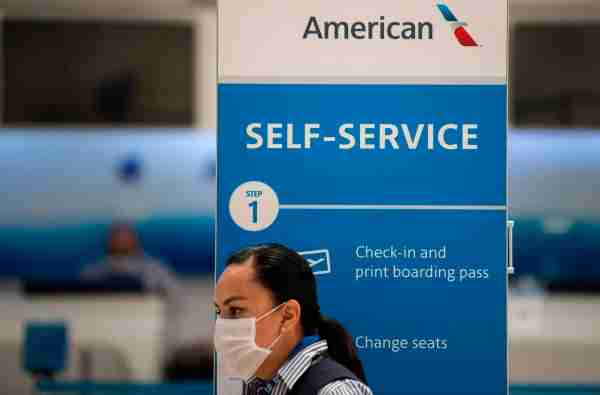 An American Airlines staffer waits for customers at the Benito Juarez International airport, in Mexico City, on May 20, 2020, amid the new Covid-19 coronavirus pandemic. - From suspending all flights to reducing their employees