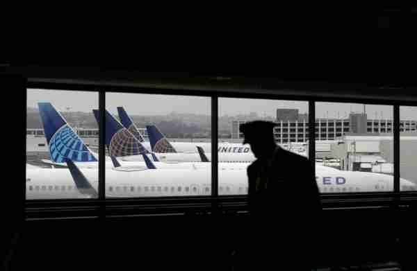 SAN FRANCISCO, CALIFORNIA - APRIL 12: A pilot walks by United Airlines planes as they sit parked at gates at San Francisco International Airport on April 12, 2020 in San Francisco, California. San Francisco International Airport has a seen a huge decline in daily flights since the coronavirus shelter in place. United Airlines, the airport