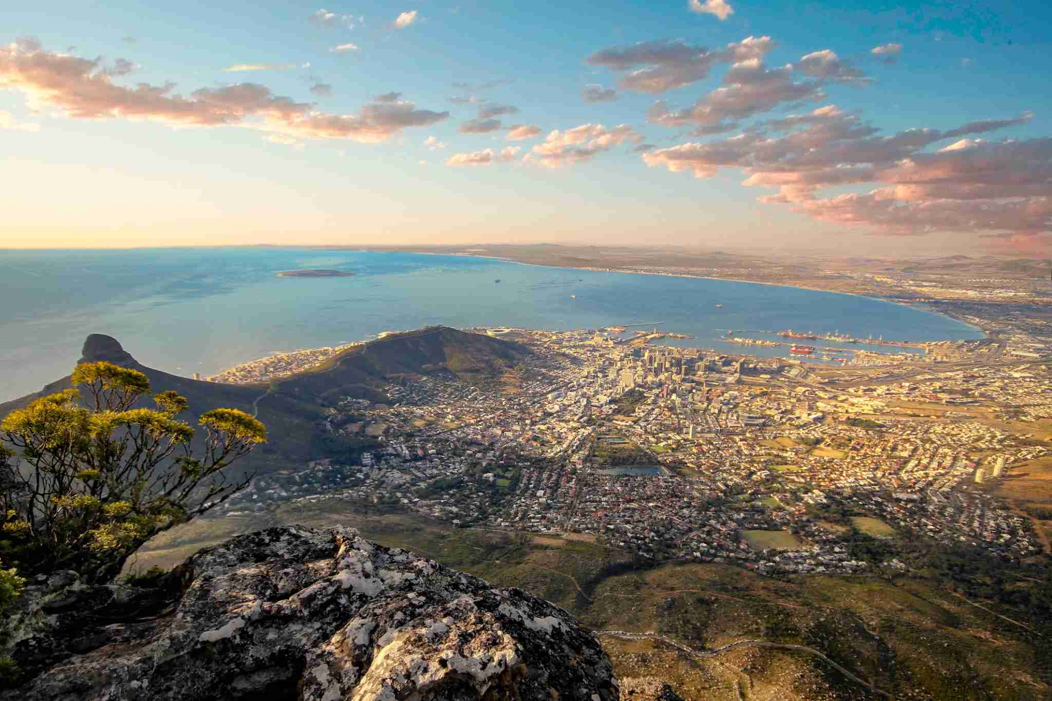 Beautiful sunset and landscape of Cape Town from Table Mountain lookout, this is the​ best sight in the city of Cape Town in South Africa, you can see everything in a clear day.This is a dramatic landscape of the area, we see some clouds and colorful sky, the sunlight is about to set and is casting some wonderful colors the city looks amazing.