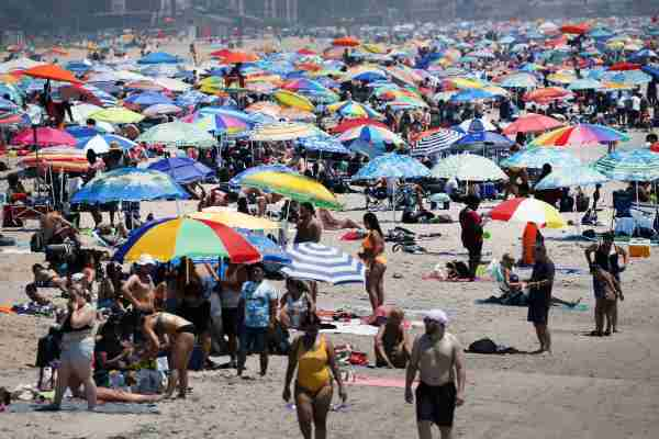 NEW YORK, NEW YORK - JULY 19: Large crowds visit the beach at Coney Island in Brooklyn on July 19, 2020 in New York City. Much of the East Coast is experiencing usually warm weather with high