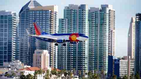 (GERMANY OUT) A Boeing 737 of Southwest Airlines approaching Lindbergh Field, with high rises of the San Diego skyline in the background.