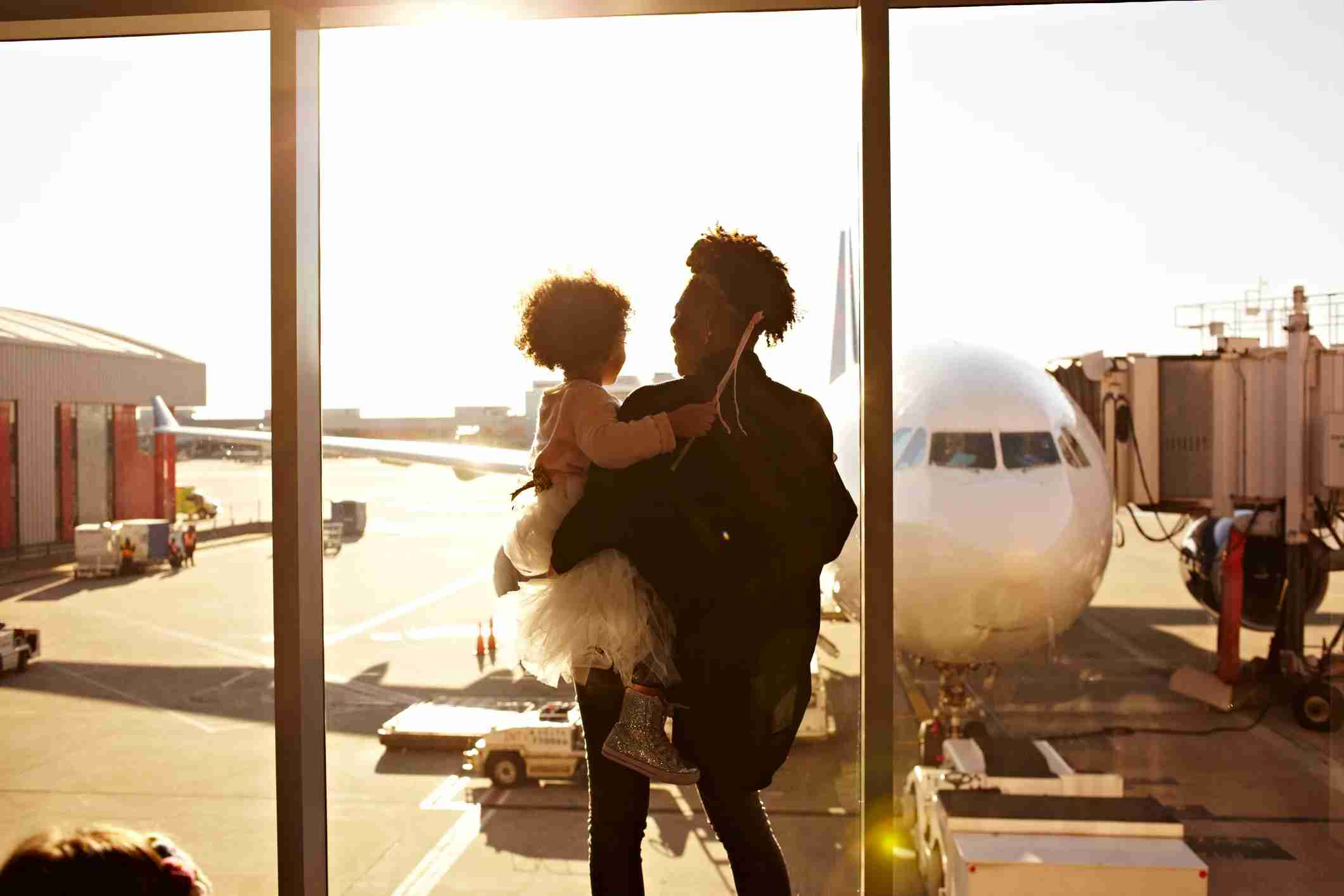 Mother holding daughter at airport. (Photo by Granger Wootz/Getty Images)