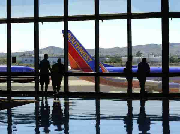 PHOENIX, AZ - SEPTEMBER 28, 2014: Airline passengers waiting for their flights watch from the terminal as a Southwest Airlines plane taxis at Phoenix Sky Harbor International Airport in Phoenix, Arizona. (Photo by Robert Alexander/Getty Images)