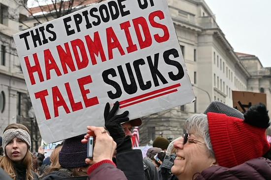 """Many protesters. One carries a sign: """"This episode of Handmaid's Tale sucks"""". Letters of the sign are black on white, except for the words from the book title, """"Handmaid's Tale,"""" which are red."""