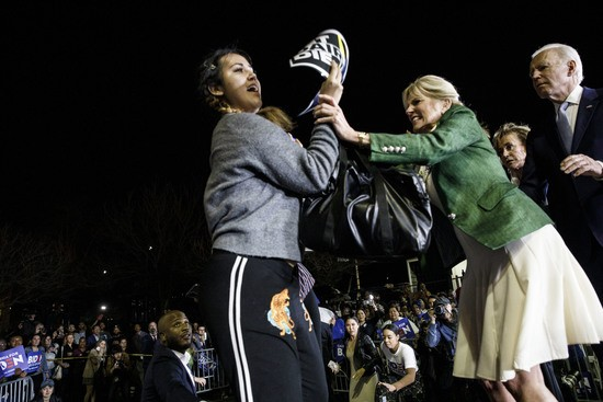 Former Vice President Joe Biden, 2020 Democratic presidential candidate, right, watches as his wife Jill Biden, center, blocks a protester from arriving on stage during an primary night rally in the Baldwin Hills neighborhood of Los Angeles, California, U.S., on Tuesday, March 3, 2020. The biggest day of the presidential primary calendar will define the nomination fight for Bernie Sanders and Biden and determine whether Michael Bloomberg and Elizabeth Warren have a rationale for carrying on their campaigns. Photographer: Patrick T. Fallon/Bloomberg