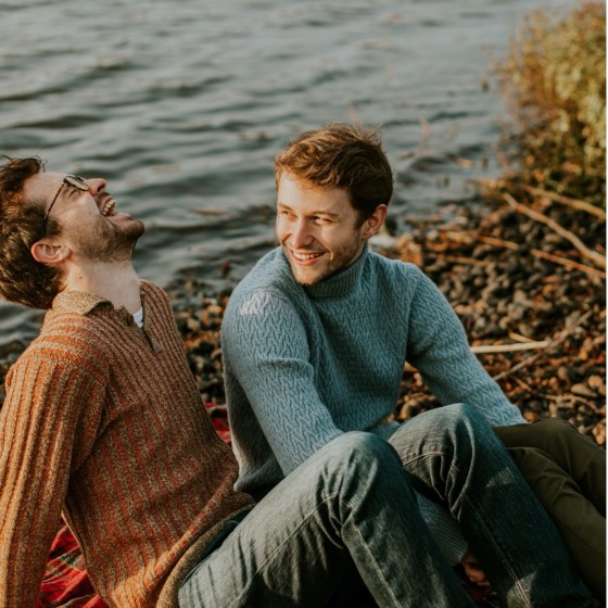 Two men laughing near a lake