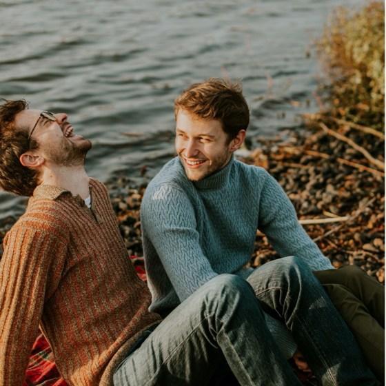 Two men laughing near a lake