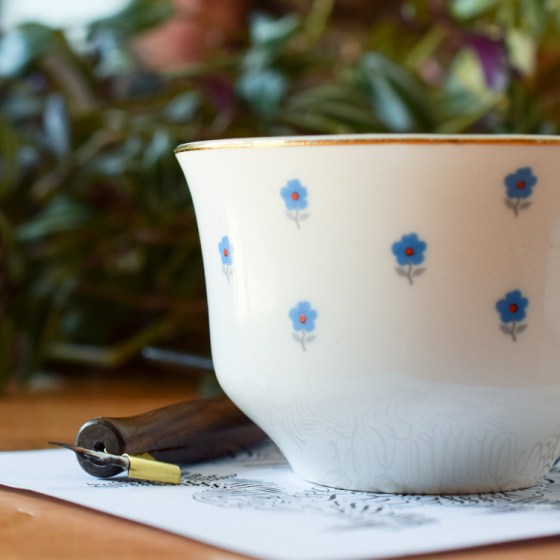 Each cup features a dainty floral pattern. The flowers are a vibrant blue with a red center.