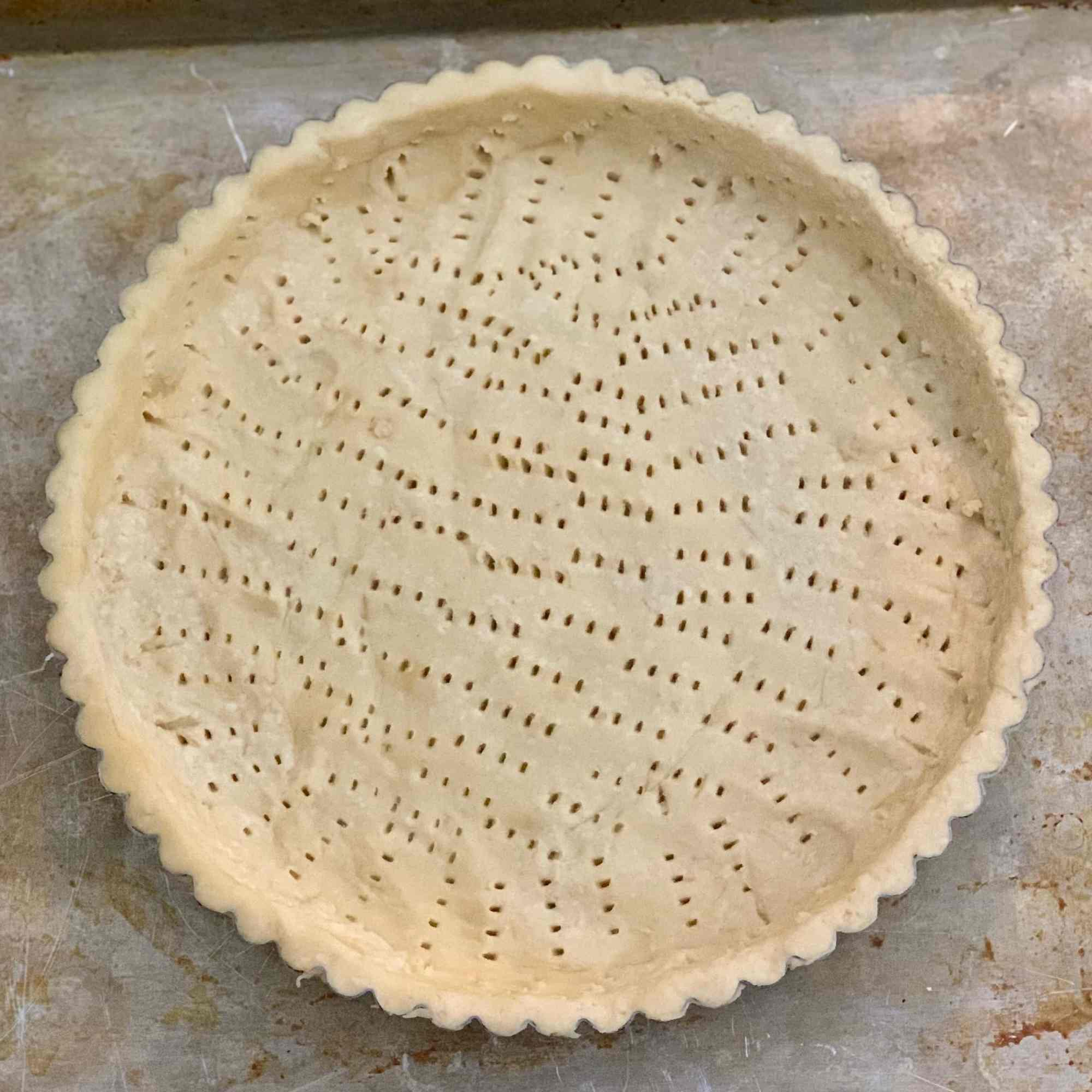 A raw tart crust pressed into a tart pan and pricked all over with a fork.