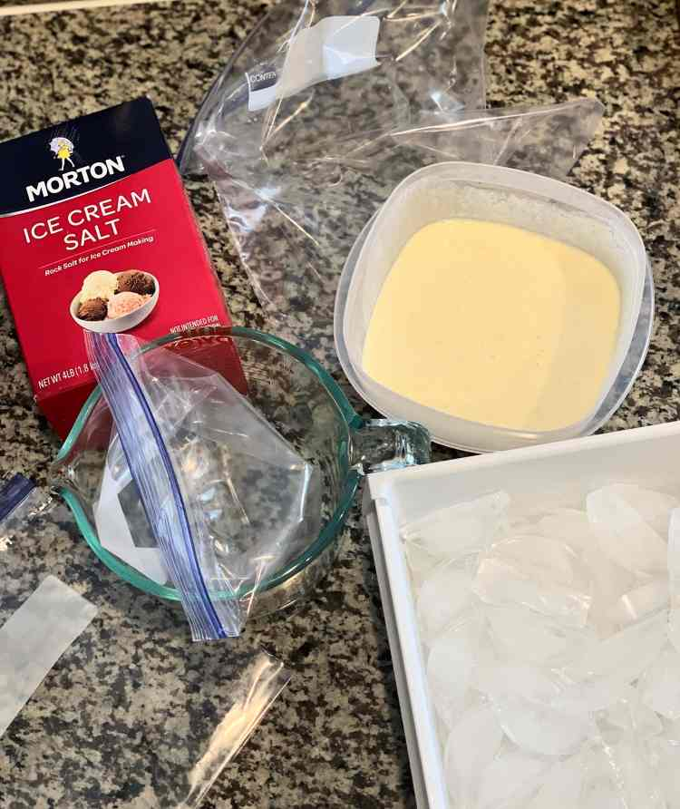 The supplies for making ice cream sit on a grey and white counter. A box of Morton ice cream salt, a gallon ziplock bag, a tupperware of chilled ice cream base, two quart-sized gallon bags, and a large container of ice cubes.