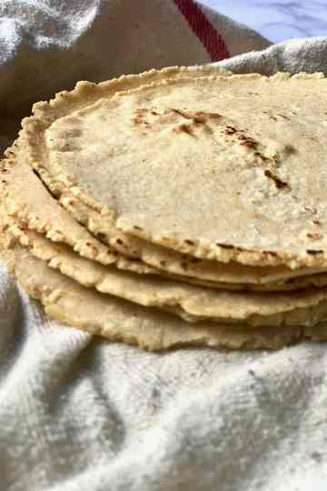a stack of corn tortillas stacked in a clean dish towel