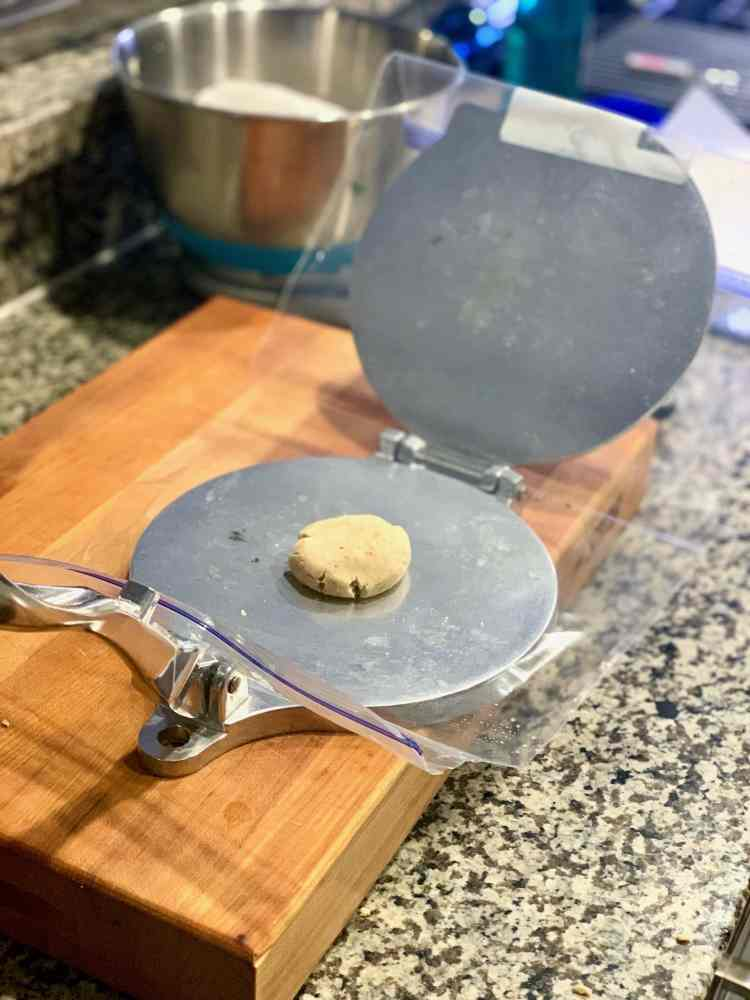 An open tortilla press sits on a wooden cutting board. It's lined with a ziplock bag that has its sides split open, and one half draped over the top plate on the tortilla press. In the center of the bottom plate is a slightly flattened dough ball.