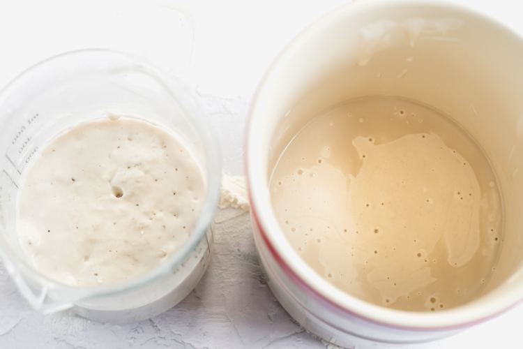 """a glass measuring cup of recent fed sourdough starter on the left. a ceramic crock of unfed """"discard"""" sourdough starter is on the right."""
