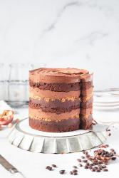 a mocha hazelnut layer cake with a slice being taken out of it on a cake lifter spatula