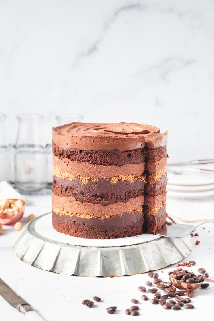 Close up of the side/bottom of Mocha Hazelnut cake. The cake is sitting on a wide, flat black plate with an upturned rim. The plate has 6 loose hazelnuts on it.