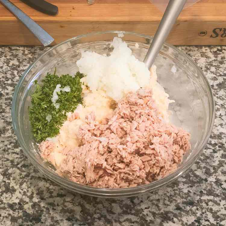 A clear glass bowl sits on the kitchen counter. It's filled with mashed potatoes, tuna, chopped parsley, and grated onion. A muddler sticks out of the top right of the bowl.