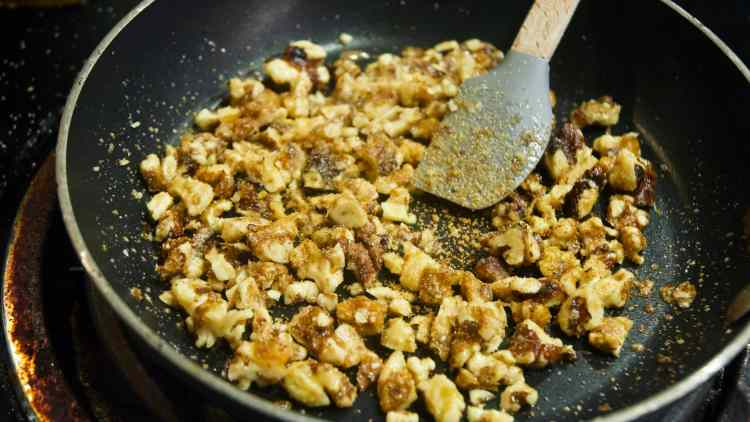 A close-up shot of roughly chopped walnuts toasting in a small non-stick skillet. The walnuts are covered in garlic powder and salt. A small spatula with a grey silicone paddle rests in the middle of the pan.